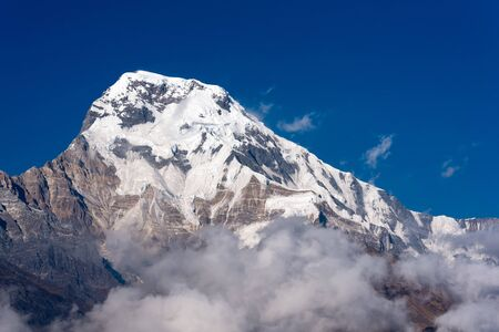 Annapurna South mountain peak with blue sky background in Nepal