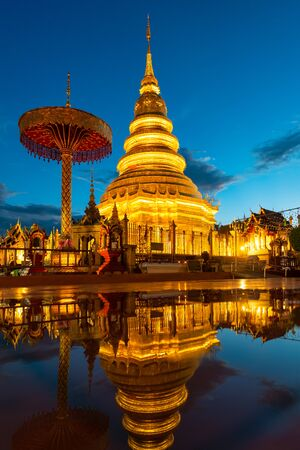 Wat Phra That Hariphunchai with water reflection in Lamphun, Thailand