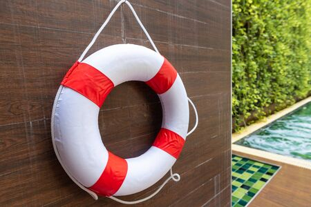 Safety torus or lifebuoy hanging on wooden wall at Swimming pool.Swimming is very popular sport in summer season Stok Fotoğraf