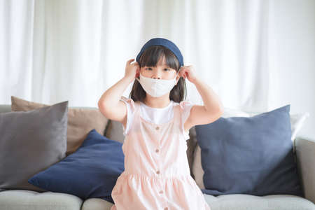 Asian little cute girl wearing hygienic face mask for prevent outbreak keep social distancing and stay at home.