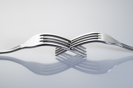 Balance view of two forks with their reflection Stock Photo