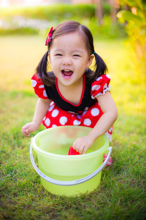 Cute Asian little girl laughing and playing in the garden Stock Photo