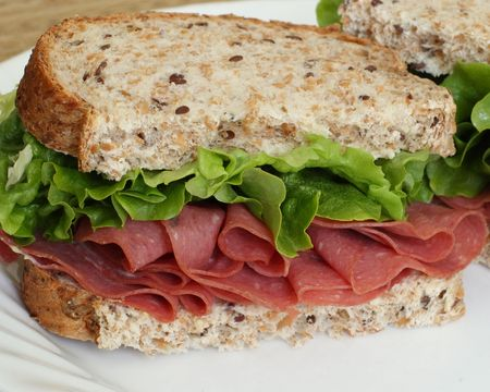 delicious corned beef sandwich with fresh leaf lettuce on multi-grain bread.