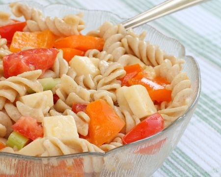 Colorful pasta salad made with spiral multigrain pasta, fresh vegetables, cheddar cheese and dijon dressing. served in a glass dish on a green and white tablecloth.  Foto de archivo