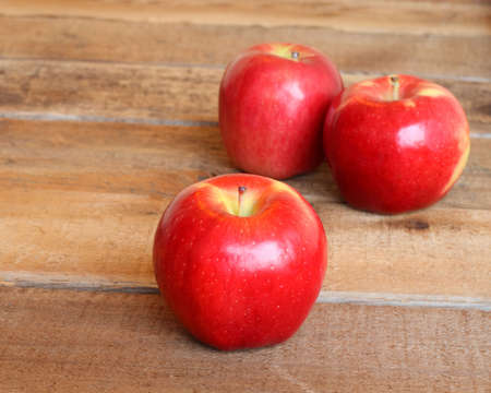 three ripe red apples on a rustic wooden background with selective focus on the apple in front photo