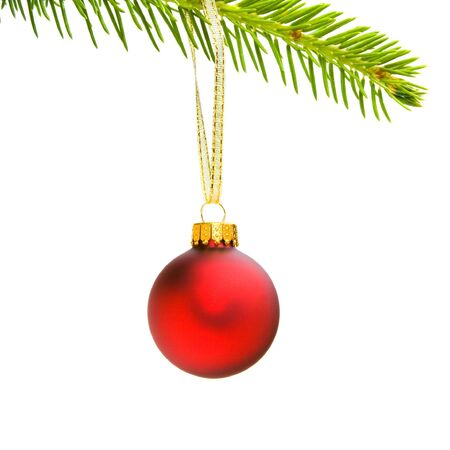 shiny red christmas ornament hanging from evergreen branch by gold ribbon