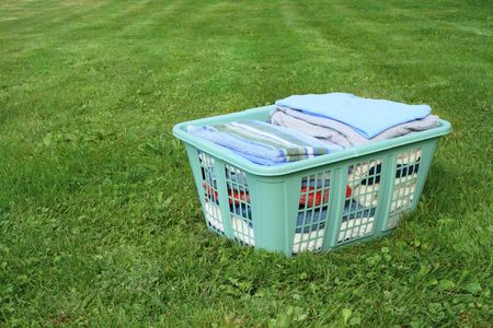 neatly folded laundry in plastic laundry hamper on lawn