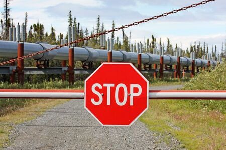 metal gate with stop sign blocks access to oil pipeline. shallow depth of field with focus on stop sign Stock Photo