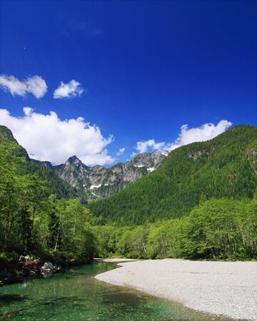 provincial: beautiful image of creek with gravel beach, forest and mountains with blue sky. taken in Golden Ears Provincial Park Stock Photo
