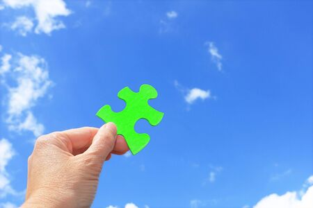 womans hand holding green jigsaw puzzle piece against blue sky
