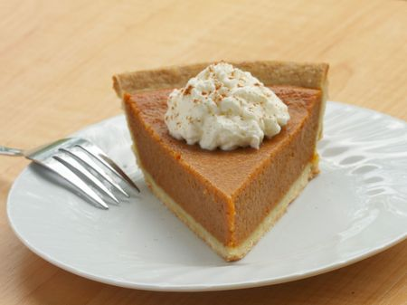 slice of pumpkin pie with whipped cream and sprinkled with cinnamon served on a white plate Foto de archivo