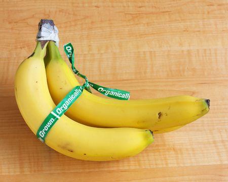 organically: bunch of organically grown bananas on wooden counter