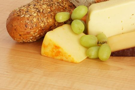 a selection of cheeses with multigrain baguette and grapes on wooden board