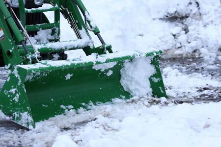 a tractor with snow blade plows a driveway