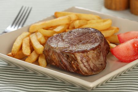 baseball cut sirloin steak with french fried potatoes and tomato wedges