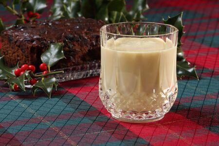 glass of eggnog and christmas fruitcake