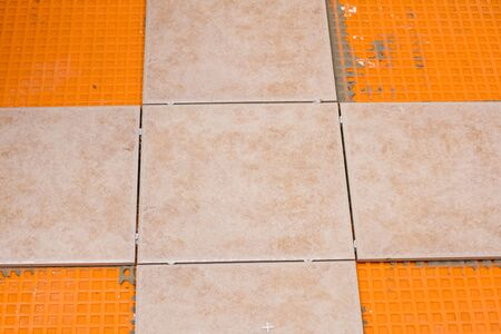 ceramic tiles laid out in a cross starter pattern for bathroom floor tiling project. the tiles are being installed over a waterproof membrane.