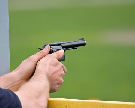 close-up of a male police officer's hands holding a gun ready to shoot