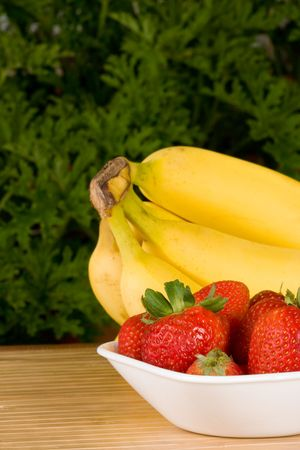 organic strawberries in a white bowl with a bunch of organic bananas behind. selective focus on the strawberries. photo