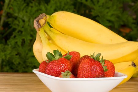organic strawberries in a white bowl with a bunch of organic bananas behind. selective focus on the strawberries. Foto de archivo