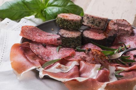 tabla de quesos: Un conjunto de varias carnes francesas e italianas en las placas de metal de época, servido con vino blanco, hierbas y crutones