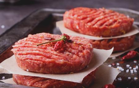 Raw Ground beef meat Burger steak cutlets with seasoning on vintage metal tray, black background
