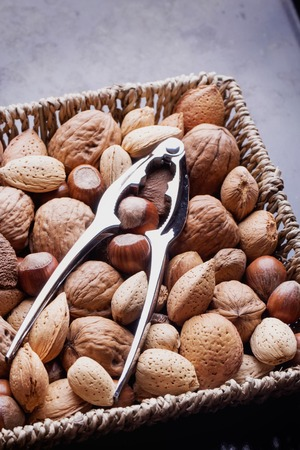 nut cracker: Selection of various nuts: almonds, Brazilian, walnuts on a vintage square basket with a nut cracker