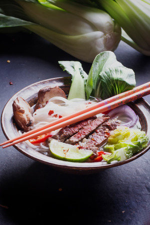 chop sticks: Vietnamese Pho Bo soup served in vintage oriental bowl with chop sticks, seasoning and greens on background Stock Photo