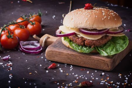 freshly cooked: Home made freshly cooked burger with seasoning, vegetables and greens on wooden board, black background