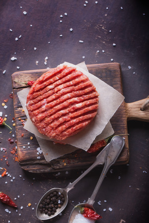 Raw Ground beef meat Burger steak cutlets with seasoning on vintage wooden boards, black background