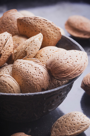 cobnut: Selection of almonds in the vitage copper chinese bowl, black background