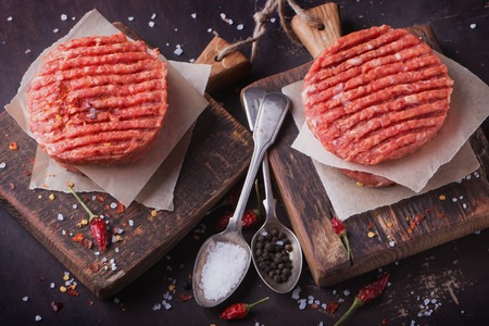 black boards: Raw Ground beef meat Burger steak cutlets with seasoning on vintage wooden boards, black background