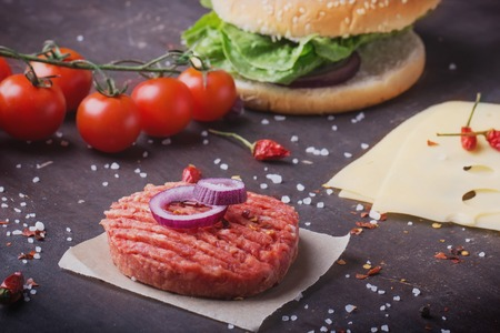 onion rings: Raw Ground beef meat Burger steak cutlets with seasoning, buns, cheese, tomatoes, onion rings and salad on  black background,