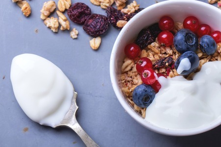 Home Made Granola breakfast with white plain yogurt, blueberries, redcurrant and dry cherries on metal background Фото со стока