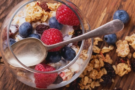 Home Made Granola breakfast with white plain yogurt, blueberries, raspberries and dry cherries on rustic wooden background