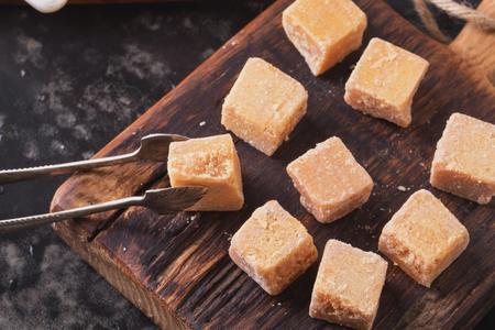 azucar: Tableros de madera rústica con un tazón de azúcar cristal de caramelo dulce de azúcar, servido con terrones de azúcar sobre fondo oscuro