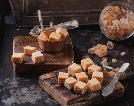 fudge: Rustic wooden boards with fudge candy glass sugar bowl, served with sugar cubes over dark background