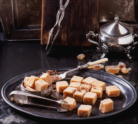 Vintage metal tray with fudge and truffle candies  glass sugar bowl, served with chocolate chips over dark background