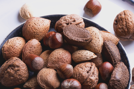 cobnut: Selection of almonds in the vitage ceramic plate, black background, top view