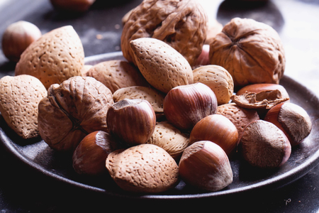 cobnut: Selection of almonds in the vitage ceramic plate, black background Stock Photo