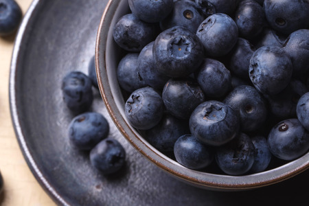 acai berry: Fresh blueberries in the vintage  blue cup on a rustic creamy wooden board