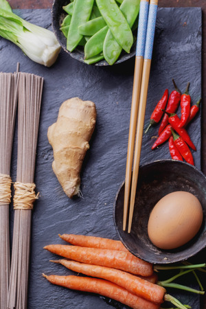 chop sticks: Ingregients for japanese soba stir fry: dry soba noodles, carrots, green pears, red chili, ginger, egg and chop sticks on the slate board