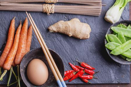 chop sticks: Ingregients for japanese soba stir fry: dry soba noodles, carrots, green pears, red chili, ginger, egg and chop sticks on the slate board