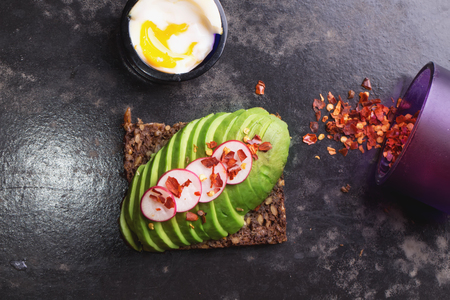raddish: Open sandwich: avocado with raddish and chili flakes, soft boiled egg and chili flakes in a bowl