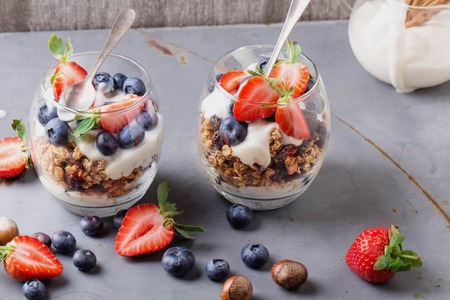 Home made granola breakfast with strawberries and bluberries and plain yogurt, served in the glasses over a blue metal background