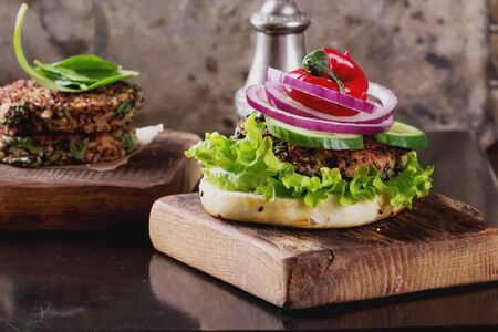 vegetarian hamburger: Veggie quinoa burgers with  lettuce, tomato and spinach Stock Photo