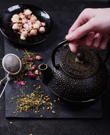 lifted hands: Traditional eastern metal teapot lifted by male hands with the variety of tea, infused with herbs and flowers over the black stone slate board