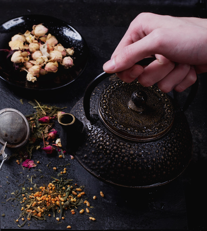 lifted hands: Traditional eastern metal teapot lifted by male hands with the variety of tea, infused with herbs and flowers with bamboo mat and chop sticks over the black stone slate board Stock Photo