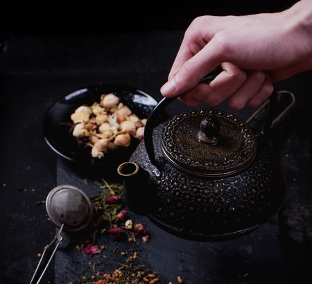 chop sticks: Traditional eastern metal teapot lifted by male hands with the variety of tea, infused with herbs and flowers with bamboo mat and chop sticks over the black stone slate board Stock Photo
