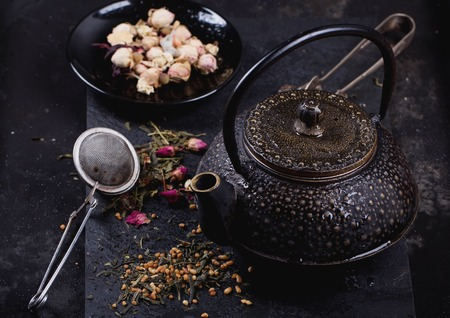 chop sticks: Traditional eastern metal teapot with the variety of tea, infused with herbs and flowers with bamboo mat and chop sticks over the black stone slate board